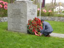 Bayram Yerli (Ortsvereinsvorsitzender) legt einen Blumenkranz am Denkmal zum 28. April 1945 nieder