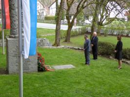 """Bayram Yerli (Ortsvereinsvorsitzender), Hans Mummert (Altbürgermeister) und Elke Zehetner (ehemalige Erste Bürgermeisterin) gedenken der Opfer der """"Penzberger Mordnacht"""" am Denkmal zum 28. April 1945"""